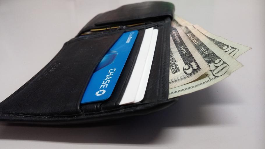 otevřená pánská peněženka s bankovkami a kreditkou